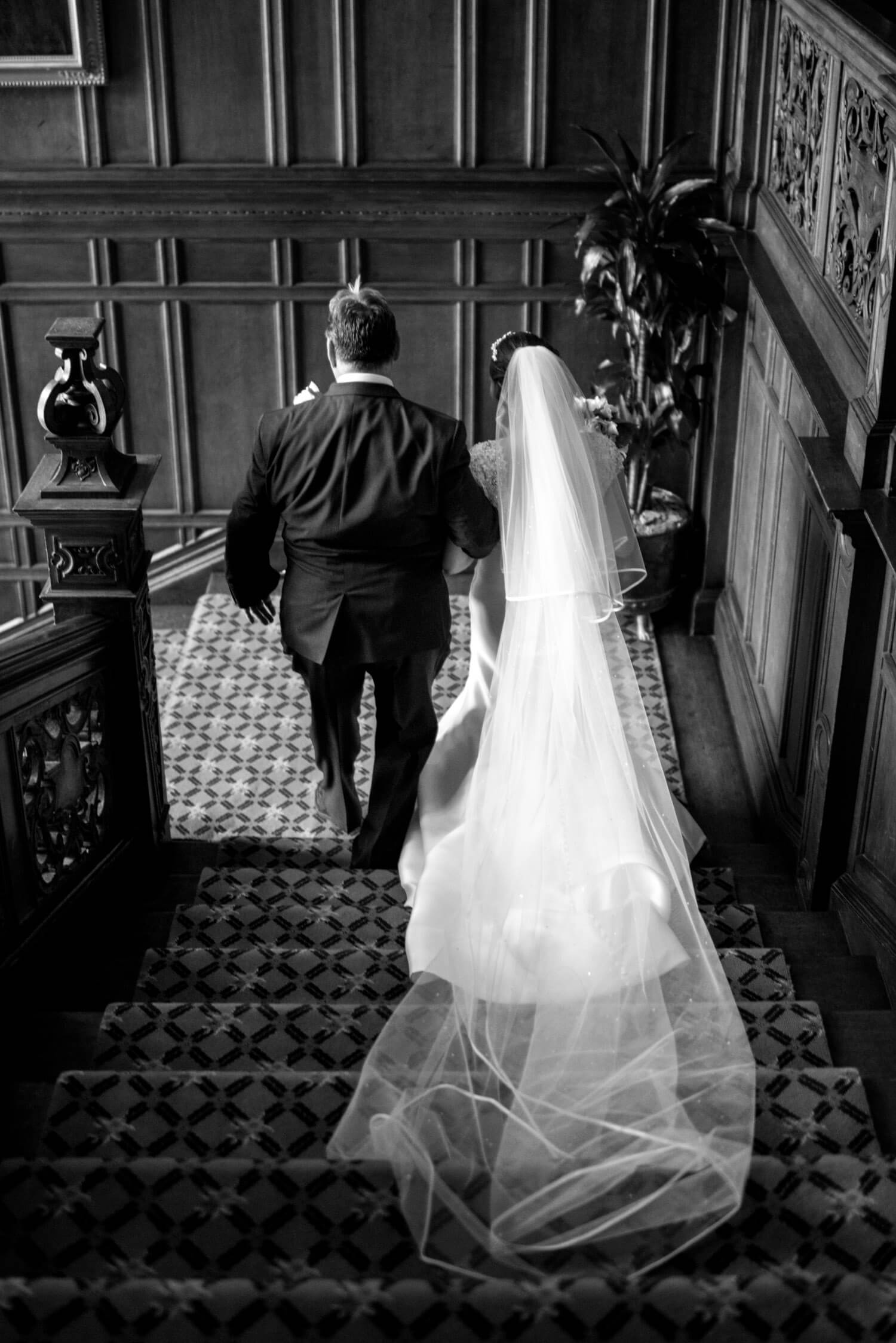 Father walks daughter bride down stairs at Tylney Hall