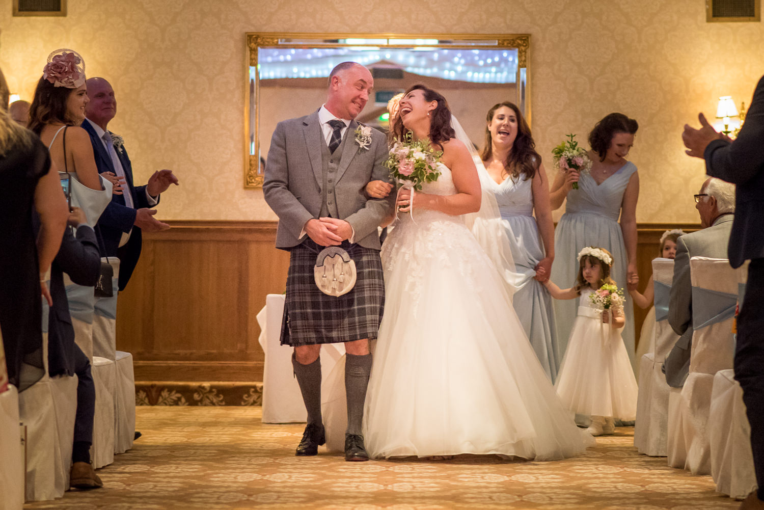 Bride and groom walking down the aisle at Ashdown Park Hotel
